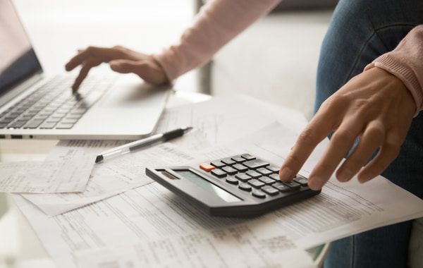 Woman calculating monthly expenses