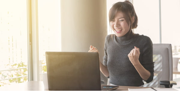 Woman who sitting work by notebook in feeling happy