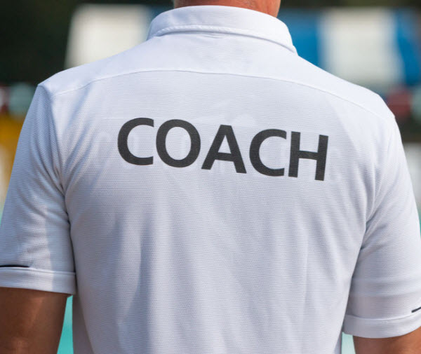 AS - a man wearing a white shirt with a word coach on it