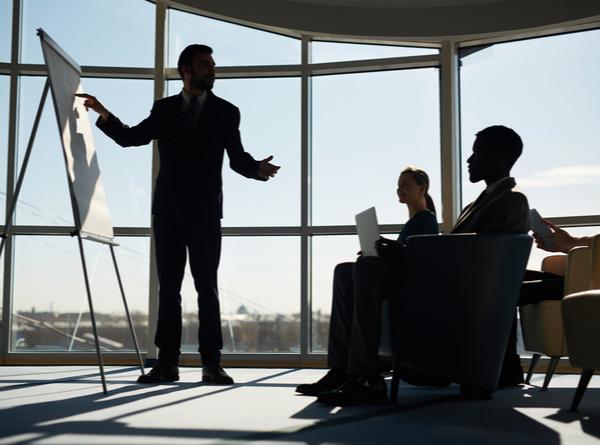 AS - Confident man pointing at blank whiteboard at seminar