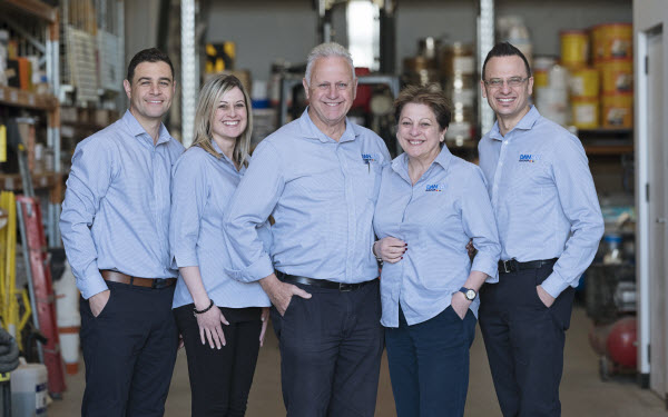 Five colleagues having a group picture inside the factory